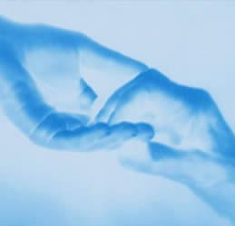 En la imagen dos manos una joven y otra de persona mayor rozándose